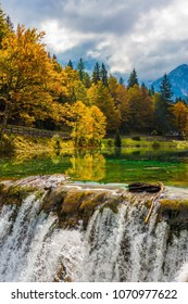Small waterfall on the picturesque quiet lake Lago de Fusine in the mountain valley. The beautiful forests. Flood after rain. Concept of cultural and ecological tourism