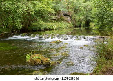 Small waterfall on River Dove running through steep hills in Dovedale, Derbyshire UK