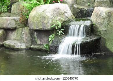 Small waterfall in public tropical garden.