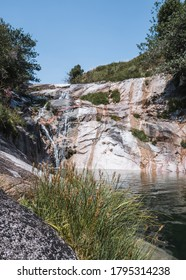 Small waterfall in streaked orange rock, flowing to a clear green pond surrounded by rocks, trees and vegetation, in Xertelo, Geres National Park