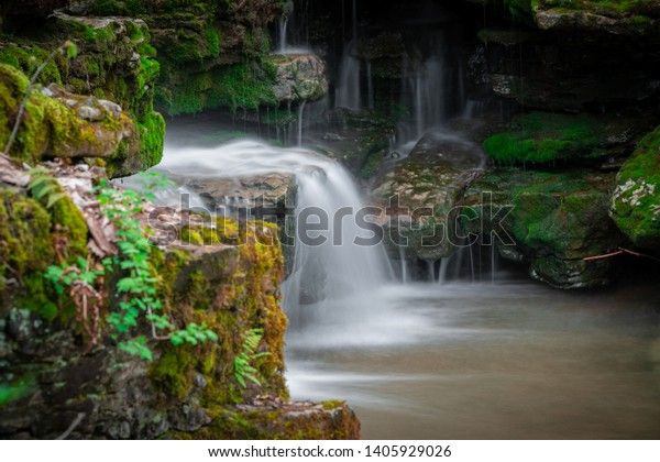 Small waterfall and stream draining into a small pool surrounded
