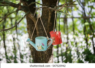 small watering can hanging on the tree