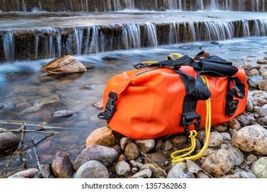 small waterproof duffel on a rocky river shore below a dam