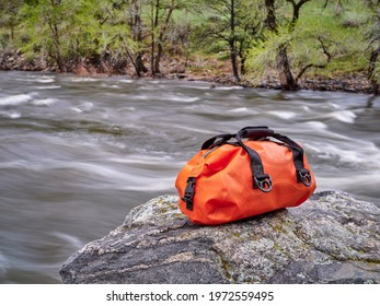 small waterproof duffel on a rocky river shore - Poudre River in a canyon above Fort Collins, Colorado, in springtime scenery