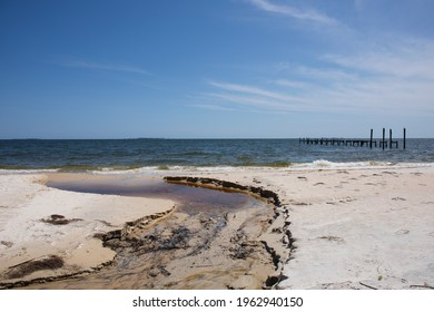 A small watery estuary with wooden pylons in the Gulf of Mexico.  Blue sky, blue ocean waves and wooden structures in the water with light surf