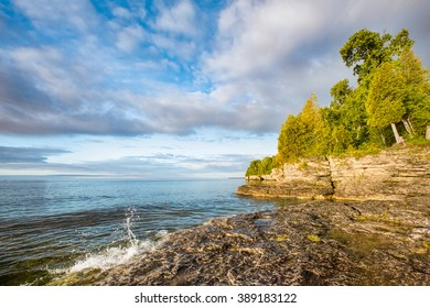 A small wave breaks and splashes under a cloudy blue sky at Door County, Wisconsin's Cave Point on the coast of Lake Michigan.