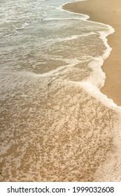 Small waves on sandy beach on Atlantic ocean coast in a sunny summer day