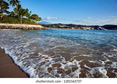 Small waves washing the sand of Manzanilla beach at Bays of Huatulco in Oaxaca, Mexico, on a beautiful sunny morning. On the background Tangolunda bay with a few hotels on the shoreline.