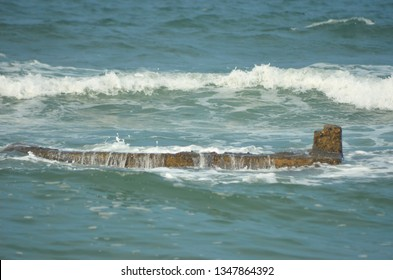 Small waves and white foam are washing over a rock shelf in the ocean. The rocks are brown and nearly fully submerged. The water is blue, and fills the photo.