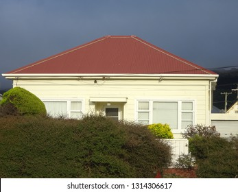 Small weatherboard cottage in bright sunlight showing red roof  and garden hedge against stormy grey sky Petone New Zealand