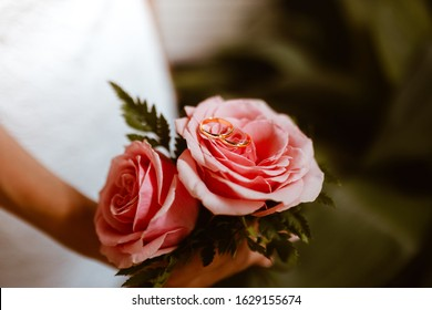 Small wedding bouquet of pink roses with wedding rings on the top. Wedding day concept.