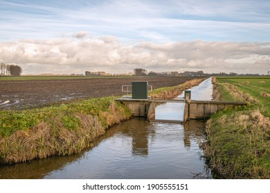 Small weir in a ditch in a Dutch polder. The weir is operated from a distance by the water board. The photo was taken in the province of Noord-Brabant on a slightly cloudy day in the winter season. - Shutterstock ID 1905555151