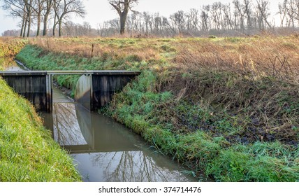 Small weir of wood and steel ditch in a Dutch polder. The light and the mirror-smooth surface cause particular reflections.