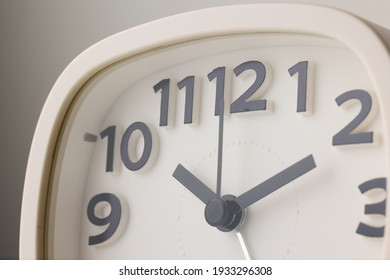 Small white alarm clock, black numbers, set the time for 10.10 o'clock, placed on a white table.