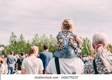 Small white blond child girl kid sitting on the fathers parent shoulders in the summer day with people walking around and green trees on the background
