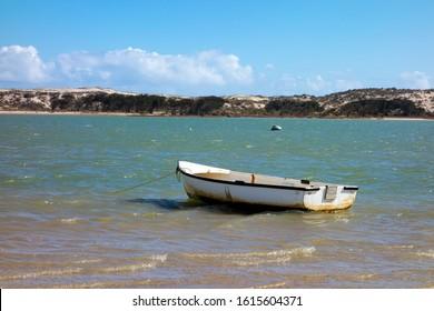 A small white boat left anchored in Lake Magic in Western Australia near Hyden