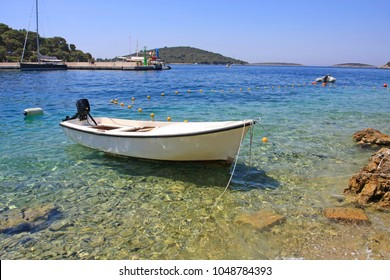Small white boat in shallow port with azure sea in Croatia
