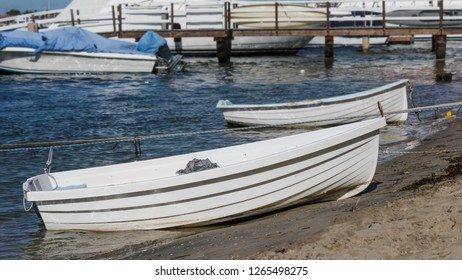 Small white boats tied with rope on the sand. Focus on foreground boat. Blurred wooden pier in background.