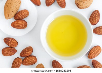 Small white bowl with almond oil and cotton pad for natural skin care. Organic cleansing oil, make up remover, nail and cuticle treatment. Top view, copy space.
