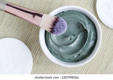 Small white bowl with blue cosmetic clay mask. Homemade beauty treatment. Top view, copy space.