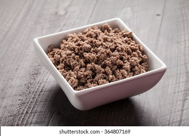 Small white bowl of cooked ground meat on brown wooden table