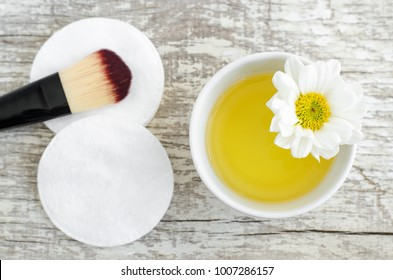 Small white bowl with cosmetic/cleansing oil and cotton pad for natural skin care. Homemade cosmetics.