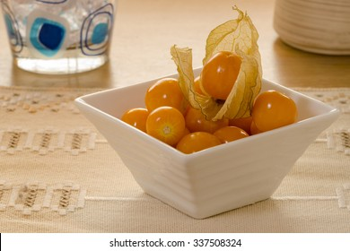 A small white bowl, full of physalis, with one still in it´s thin and fragile shell standing on a kitchen table