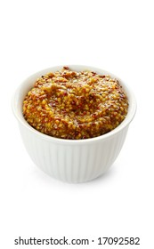 Small white bowl of whole-grain seeded mustard, isolated on white.