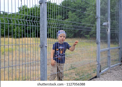 A small white boy is looking through the fence of the grate.