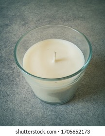 small white candle in a glass jar