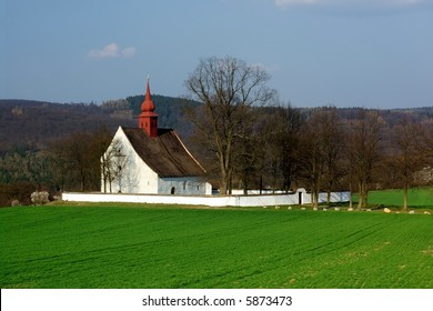 Small white chapel in green field
