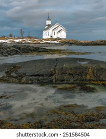 A small white Church with a cemetery stands on the shore of the fjord - Lofoten Islands, Norway