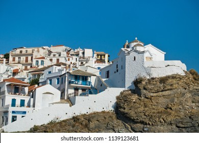 Small white church on a hill over Skopelos town at summer morning, island of Skopelos, Greece
