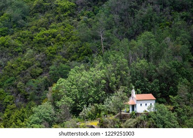 Small white church set in a lush forest landscape on a steep mountainside in the Serra da Lousa mountains in Portugal