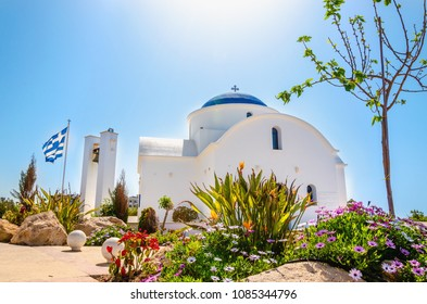 A small white church surrounded by colorful flowers against the sea