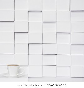 small white coffee Cup in negative space on white papercraft bricks texture background
