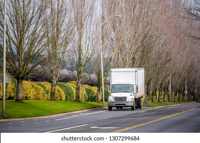 Small white compact useful transportation commercial light-duty local haul rig truck with box trailer transporting local goods on the city road with tree alley and railroad
