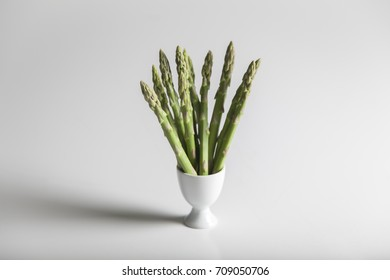 small white cup full of asparagus spears on a white background. Horizontal composition with long shadow on left side of image.