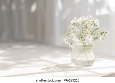 Small white daisies in a glass jar on a white tabletop.