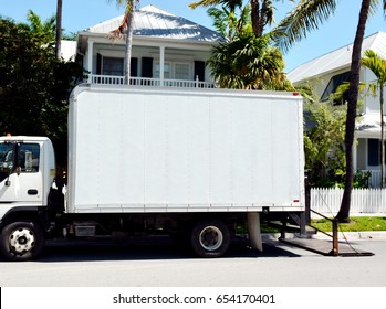 A small white delivery, or moving truck, on a residential street with lift gate lowered onto the street.