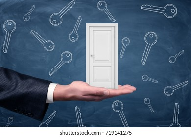 A small white door resting on a large businessman's palm with many keys drawn on a blackboard background. Key from new home. Apartment hunt. Mortgage.