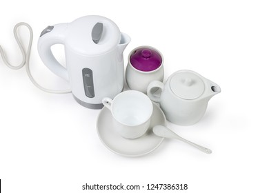 Small white electric kettle, teapot, sugar bowl and empty cup with ceramic tea spoon on saucer on a white background