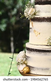 Small white flowers, macaroons, and gold-wrapped chocolates decorate a white wedding cake with layers of dark chocolate. The focus is on the foreground, with fairy lights and trees  in the background