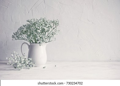 Small white flowers on a white background. Soft home decor. Gypsophila flowers. White flowers in a vase. Retro style.