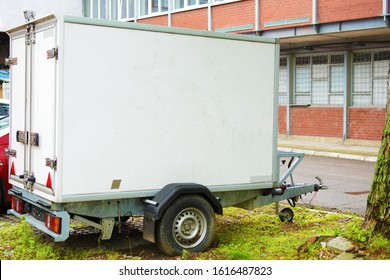 A small white fridge trailer intended for transporting fruits, fish, meat, juice, milk, drinks and other fresh produce that needs to be refrigerated and moved by car, parked on a parking lot.