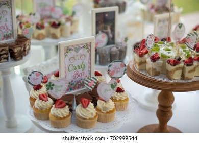 Small white and green cakes at a wedding candy bar