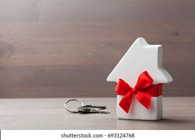 Small white house decorated red bow ribbon with bunch of keys on wooden background. Gift, real estate purchase or buying a new home concept.