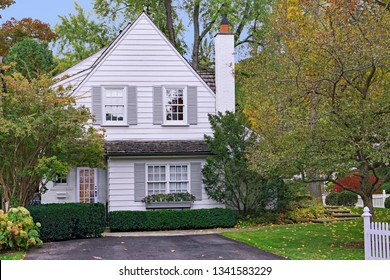 small white house with gable and picket fence surrounded by trees