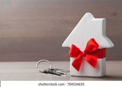 Small white house tied red ribbon and bunch of keys on wooden background. Gift, real estate purchase or buying a new home concept.