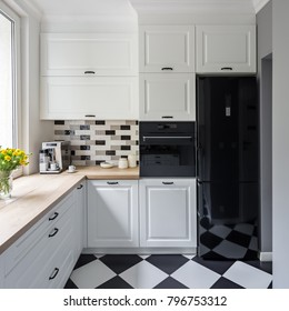 Small, white kitchen with modern chess flooring and black fridge